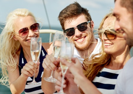 SPARKLING WINE: vacation, travel, sea, friendship and people concept - smiling friends with glasses of champagne on yacht
