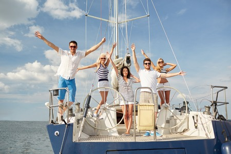 yachting: vacation, travel, sea, friendship and people concept - smiling friends sitting on yacht deck and greeting