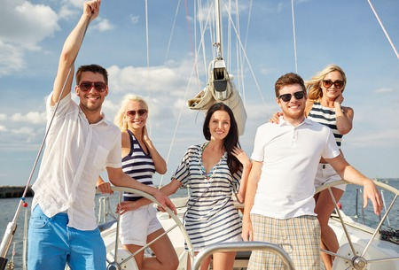 on vacation: vacation, travel, sea, friendship and people concept - smiling friends sailing on yacht