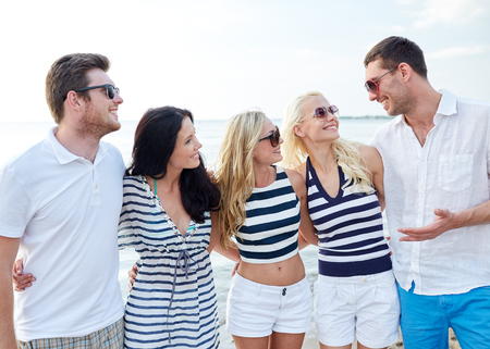 summer, holidays, sea, tourism and people concept - group of smiling friends in sunglasses talking on beach photo