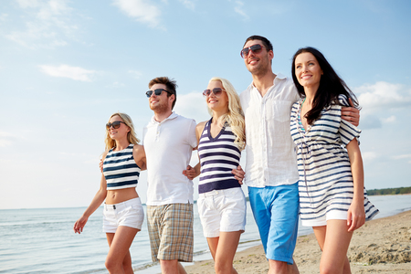 summer, holidays, sea, tourism and people concept - group of smiling friends in sunglasses walking on beach photo