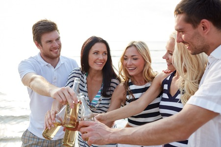 cheers: summer, holidays, tourism, drinks and people concept - group of smiling friends clinking bottles of beer or cider on beach