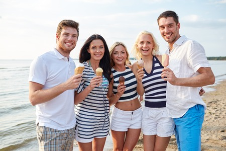 summer, holidays, sea, tourism and people concept - group of smiling friends eating ice cream on beach photo