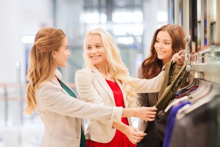 chicas de compras: venta, el consumismo y el concepto de la gente - mujeres j�venes felices que eligen la ropa en centro comercial