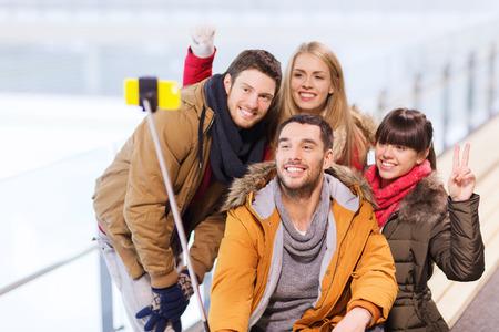 mensen, vriendschap, technologie en vrije tijd concept - gelukkige vrienden die foto met smartphone Selfie stok op ijsbaan