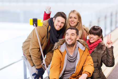 to stick: people, friendship, technology and leisure concept - happy friends taking picture with smartphone selfie stick on skating rink
