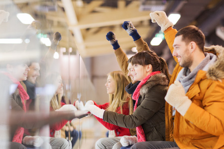 game: people, friendship, sport and leisure concept - happy friends watching hockey game or figure skating performance on skating rink