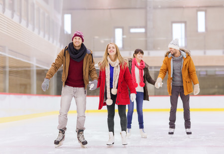 ice skates: people, friendship, sport and leisure concept - happy friends on skating rink