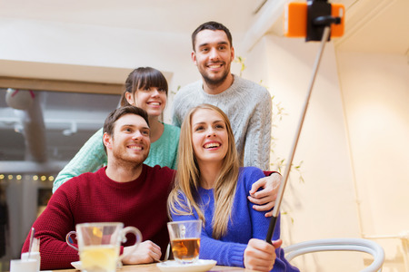 sticks: people, leisure, friendship and technology concept - group of happy friends with smartphone selfie stick taking picture and drinking tea at cafe
