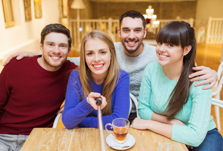 people, leisure, friendship and technology concept - group of happy friends with selfie stick taking picture and drinking tea at cafe photo