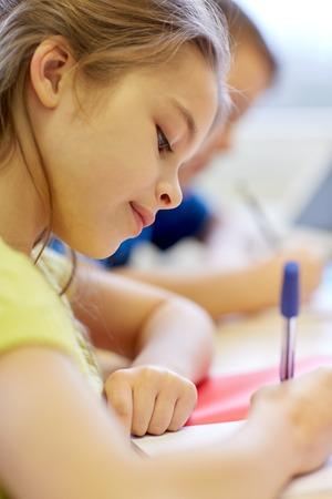 niños estudiando: educación, escuela primaria, el aprendizaje y el concepto de la gente - cerca de niños de la escuela con lápices y cuadernos de escritura de prueba en el aula