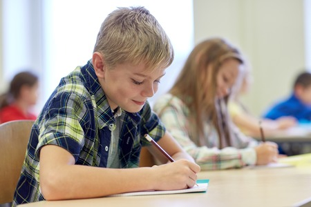 kids writing: education, elementary school, learning and people concept - group of school kids with pens and notebooks writing test in classroom