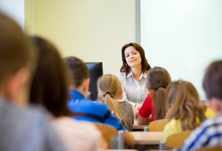 educadores: educaci�n, escuela primaria, el aprendizaje y el concepto de la gente - grupo de ni�os de la escuela con el maestro sentado en el aula