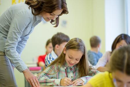 ni�as sonriendo: educaci�n, escuela primaria, el aprendizaje y el concepto de la gente - profesor de ayudar a ni�a de la escuela escrib�a la prueba en el aula