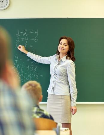 教育、小学校、教育、数学、人々 のコンセプト - 学校の子供たちと教室で緑の黒板に数学のタスクを書く教師のグループ