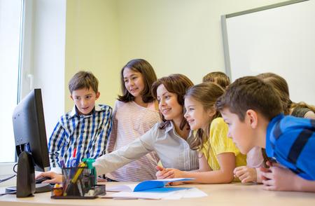maestro dando clases: educaci�n, escuela primaria, el aprendizaje, la tecnolog�a y el concepto de la gente - grupo de ni�os de la escuela con el maestro en busca de monitor de la computadora en el aula