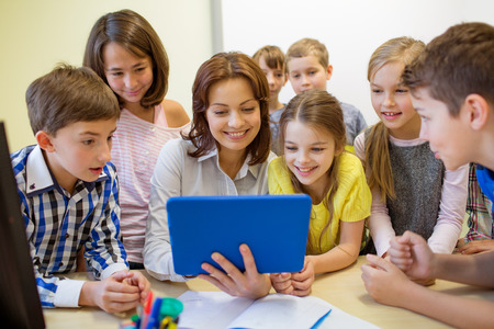 teaching children: education, elementary school, learning, technology and people concept - group of school kids with teacher looking to tablet pc computer in classroom