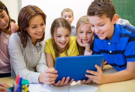 education, elementary school, learning, technology and people concept - group of school kids with teacher looking to tablet pc computer in classroom photo