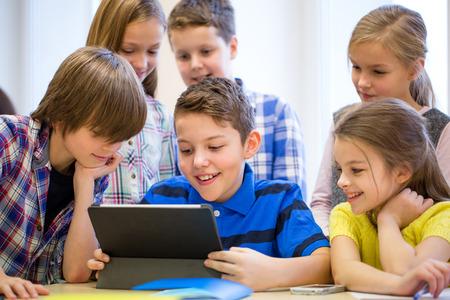aprendizaje: educaci�n, escuela primaria, el aprendizaje, la tecnolog�a y el concepto de la gente - grupo de ni�os de la escuela con la computadora Tablet PC que se divierte en descanso en el aula