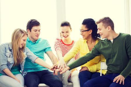 gente feliz: educaci�n y concepto de la felicidad - sonriente estudiantes en la escuela con las manos en la parte superior de cada