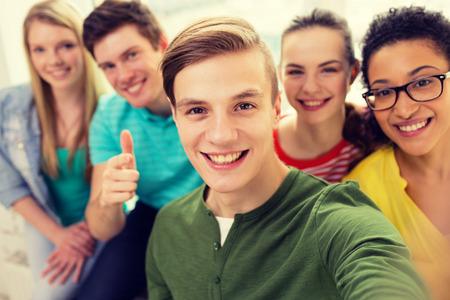 onderwijs, vrije tijd en technologie concept - vijf lachende studenten die selfie op school