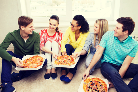 food, leisure and happiness concept - five smiling teenagers eating pizza at home Stock Photo
