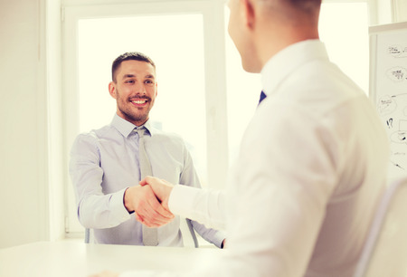 client meeting: business and office concept - two smiling businessmen shaking hands in office