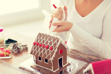 casita de dulces: la cocina, la gente, la Navidad y la decoración concepto - cerca de feliz mujer haciendo casas de jengibre en casa