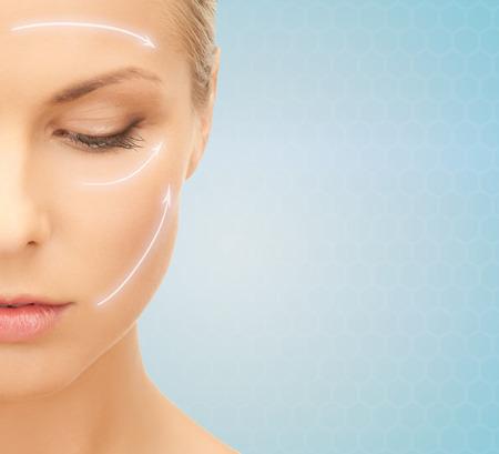 kunststoff: Schönheit, Schönheitsoperation, Alterung, Menschen und Gesundheit Konzept - schöne junge Frau Gesicht mit Hebe Pfeile auf blauem Hintergrund