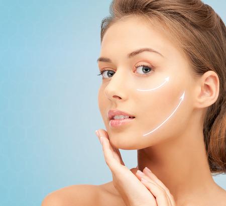 rejuvenating: bellezza, chirurgia plastica, l'invecchiamento, le persone e il concetto di salute - giovane e bella donna di toccare il viso con sollevamento frecce su sfondo blu