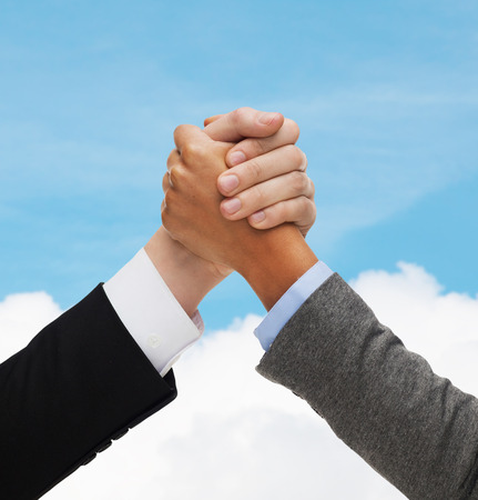 business, people and competition concept - close up of two people hands armwrestling over blue sky and white cloud background Stock Photo