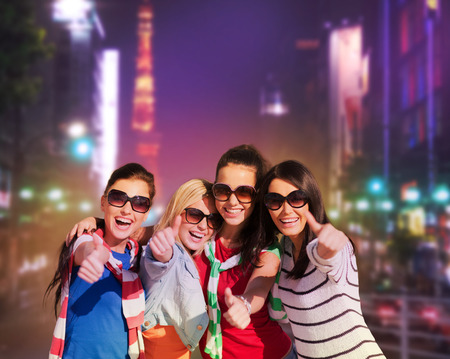 night out: summer, holidays, vacation, happy people concept - beautiful teenage girls or young women showing thumbs up in night city street Stock Photo