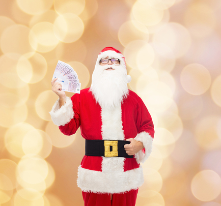 profit celebration: christmas, holidays, winning, currency and people concept - man in costume of santa claus with euro money over beige background