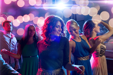 nice girl: party, holidays, celebration, nightlife and people concept - smiling friends dancing in club