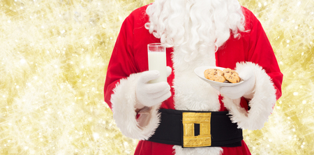 st nick: christmas, holidays, food, drink and people concept -close up of santa claus with glass of milk and cookies over yellow lights background