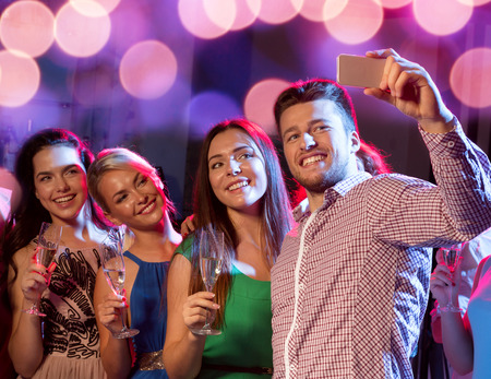 taking: party, holidays, technology, nightlife and people concept - smiling friends with glasses of champagne and smartphone taking selfie in club