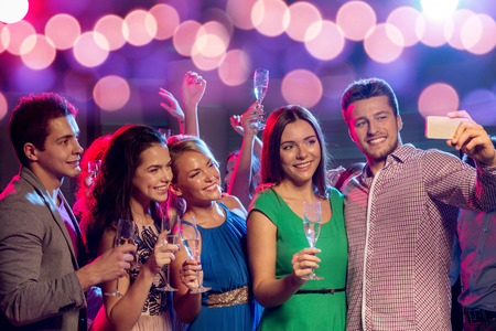 people  dancing: party, holidays, technology, nightlife and people concept - smiling friends with glasses of champagne and smartphone taking selfie in club
