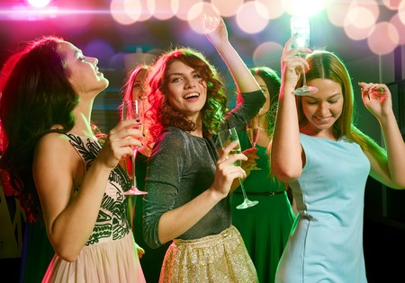 night club: party, holidays, celebration, nightlife and people concept - smiling friends with glasses of champagne dancing in club