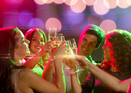 dancing club: party, holidays, celebration, nightlife and people concept - smiling friends with glasses of champagne in club