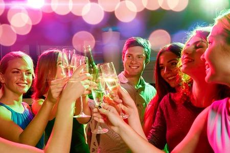 jovenes tomando alcohol: fiesta, d�as de fiesta, celebraci�n, vida nocturna y la gente concepto - sonriendo amigos que tintinean los vidrios de champ�n y la cerveza en el club