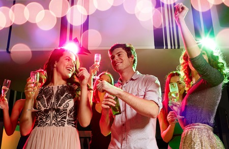 party, holidays, celebration, nightlife and people concept - smiling friends clinking glasses of champagne and beer in club photo