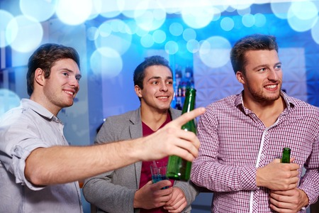 chill out: nightlife, party, friendship, leisure and people concept - group of smiling male friends with beer bottles drinking in nightclub