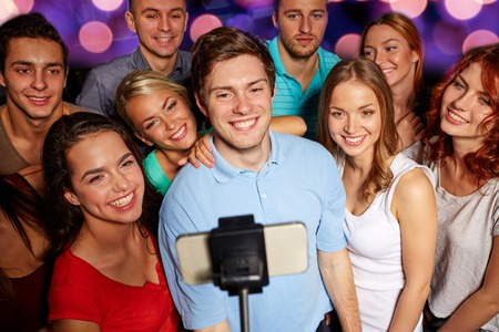 party, technology, nightlife and people concept - smiling friends with smartphone and monopod taking selfie in club Imagens - 35024253