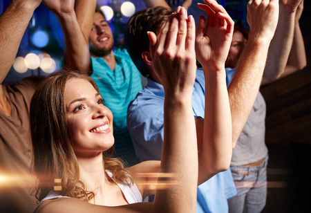 concert crowd: party, holidays, celebration, nightlife and people concept - smiling friends applauding at concert in club
