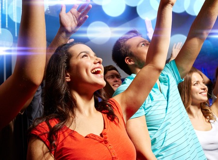party, holidays, celebration, nightlife and people concept - smiling friends waving hands at concert in club photo