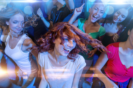 nice guy: party, holidays, celebration, nightlife and people concept - smiling friends dancing in club