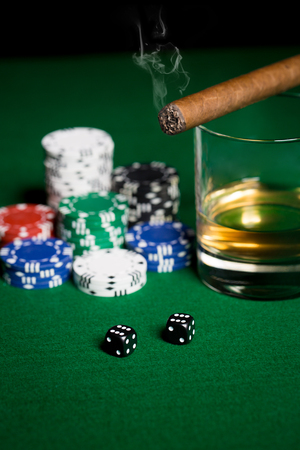 double the chances: gambling, fortune and entertainment concept - close up of casino chips, whisky glass, dice and smoking cigar on green table surface Stock Photo
