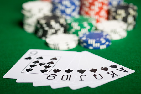 entertainment risk: gambling, fortune, game and entertainment concept - close up of casino chips and playing cards on green table surface