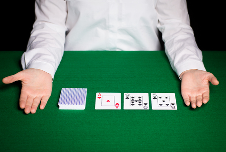 holdem: casino, gambling, poker, people and entertainment concept - close up of holdem dealer with playing cards Stock Photo