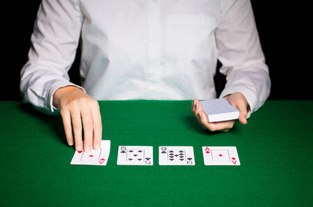 lear: casino, gambling, poker, people and entertainment concept - close up of holdem dealer with playing cards Stock Photo